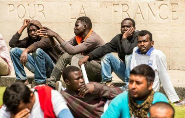 """Des migrants sont installés au pied d'un monument où est inscrit """"Pour la France"""" lors d'une """"marche pour la dignité"""" à Calais, le 20 juin 2015"""