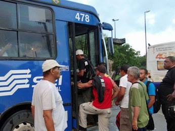 Seguranças (de camiseta e boné brancos e de camiseta preta com mão na cintura) observam embarque de passageiros (Foto: Luna Markman / G1)