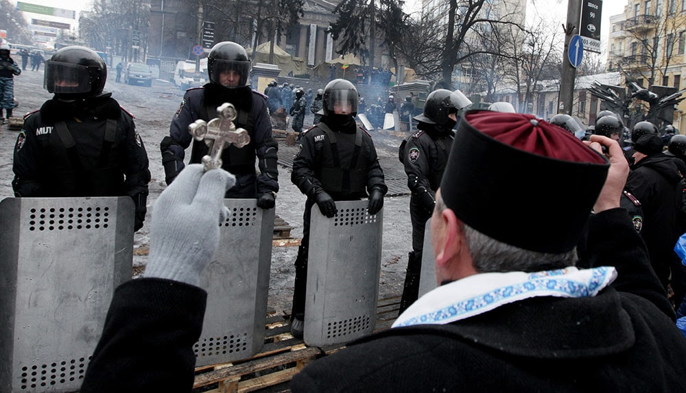 A Ukrainian priest stands in front of a line of riot police as he takes part in a protest (EPA/ZURAB KURTSIKIDZE)