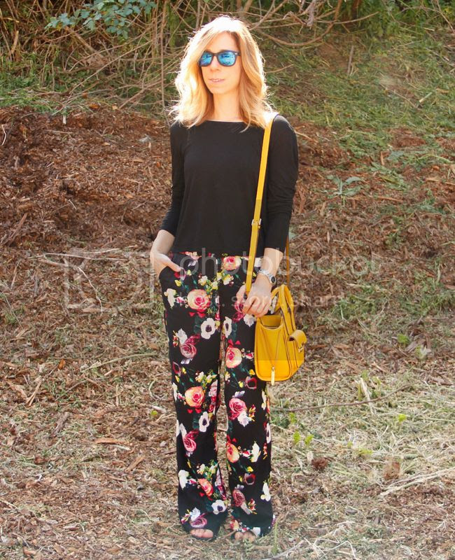 Fashion blogger The Key To Chic wears a twist back top, cage sports bra, Merona floral pants, and Sam & Libby Arianna gladiator sandals.