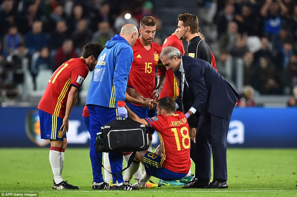 Alba receives medical attention on the pitch before an injury forces him to make way for Nacho