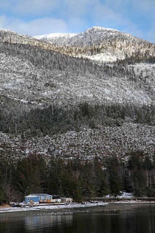 snowy scene with a house on the shore and Kasaan Mountain, Kasaan, Alaska