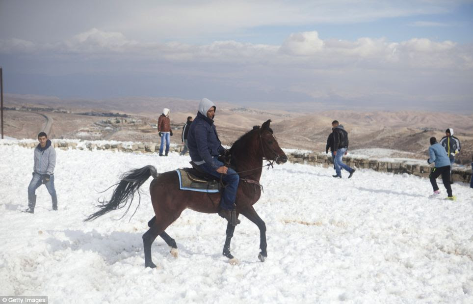 Cold blast: A Palestinian man rides his horse in the snow after heavy storms continued throughout Israel on Friday, causing traffic disruptions and power outages across the country
