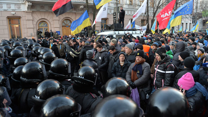 Protesters stay in front of riot policemen guarding the Ukrainian parliament in Kiev prior the parliament session on December 3, 2013. (AFP Photo/Sergei Supinsky)