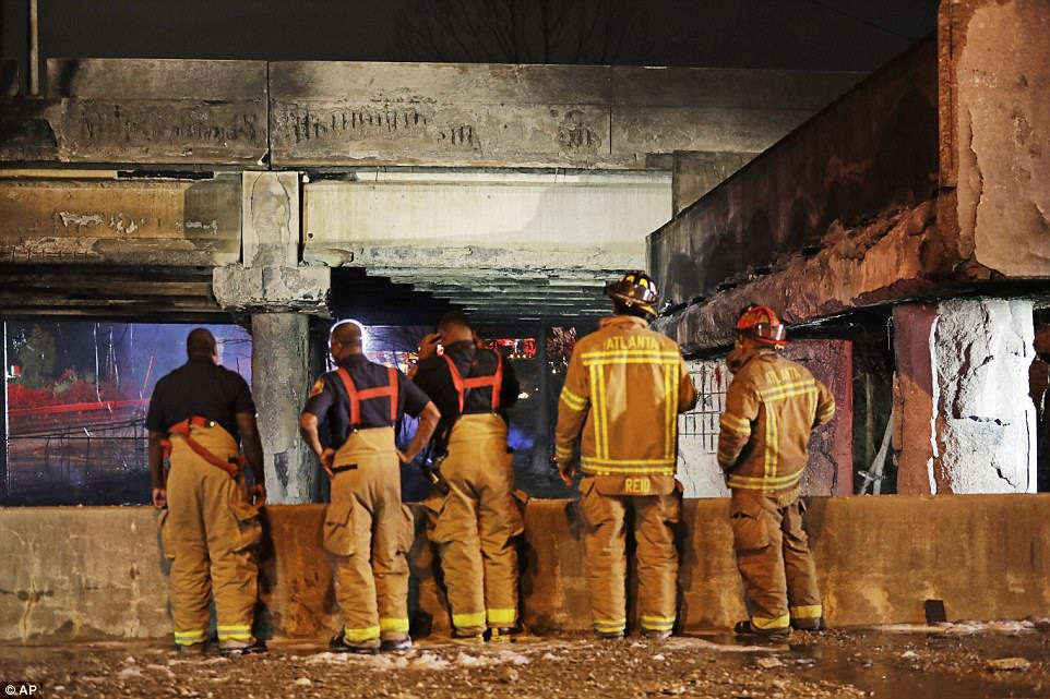 Firefighters surveyed the section of the overpass that collapsed from the large fire Thursday night