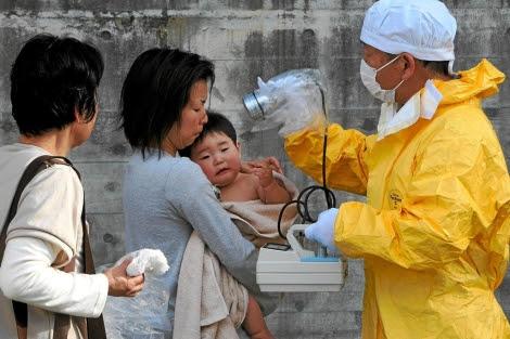Personal médico comprueba los niveles de radiación de uan mujer y su hijo. | Asahi Shimbun