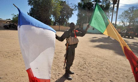 Malian soldier holds Mali and French flags