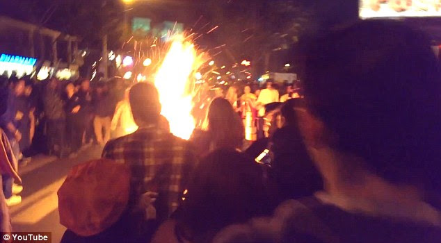 Engulfed in flames: Gilbert Estrada is in the middle of a crowd engulfed in flames