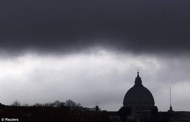 Dark rainclouds cover the area near the Vatican's Saint Peter's Basilica, in Rome today