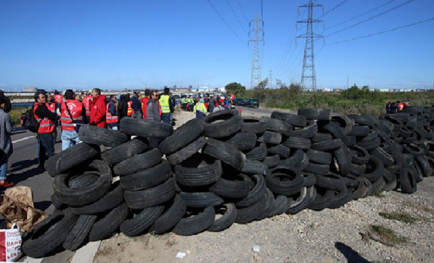 Striking union members discuss near a pile of tires as they block the entrance of a road leading to a refinery near Fos sur Mer, southern France, Monday, May 23, 2016.  Union-led blockades of French depots and oil refineries have led to fuel shortages and police action. (AP Photo/Claude Paris)