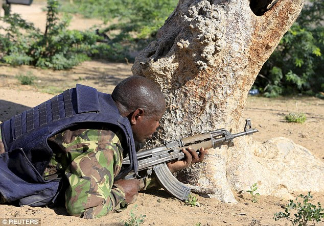 Gunfire: A Kenya Defense Force soldier takes cover near the perimeter wall of Garissa University College