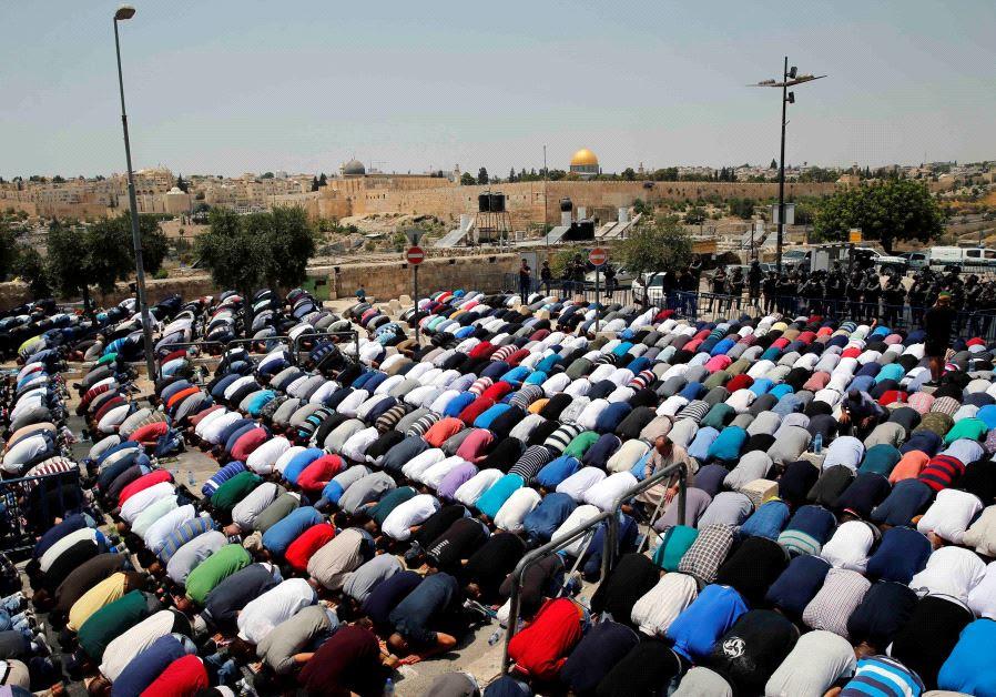 Palestinians pray on a street near a road block outside Jerusalem's Old City July 21, 2017.