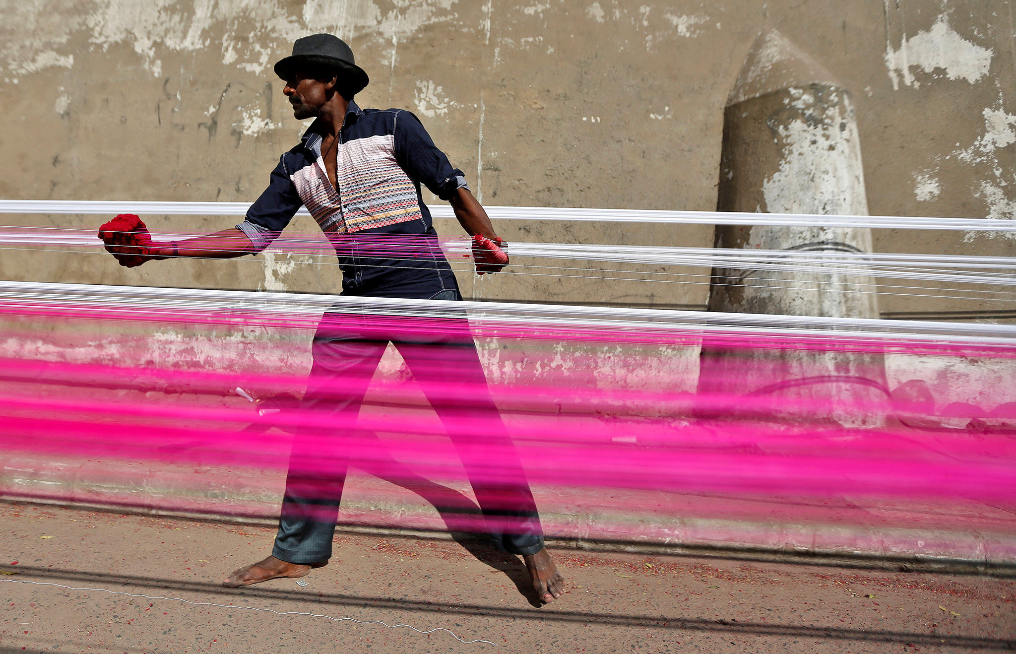 A worker applies colour to strings which will be used to fly kites, on a roadside in Ahmedabad, India, December 15, 2016. REUTERS/Amit Dave     TPX IMAGES OF THE DAY