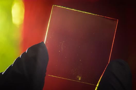 Concentrador solar luminescente transparente em comparação a um similar colorido ao fundo. Imagem © G.L. Kohuth
