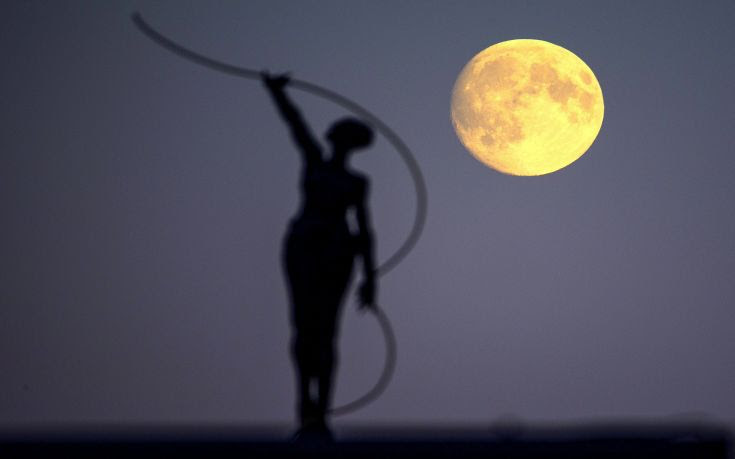 A statue is seen silhouetted against the moon in Brussels, Belgium