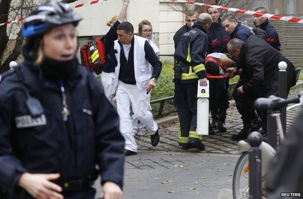 Emergency workers carry a victim on a stretcher form the scene of the shooting in Paris, 7 January