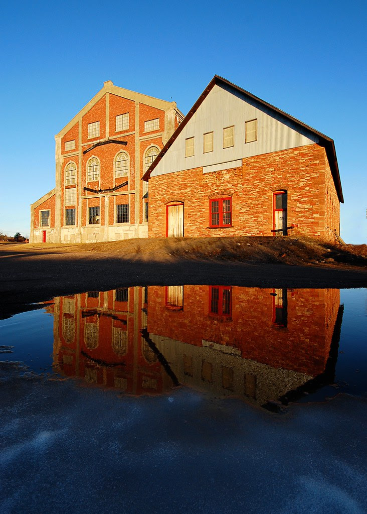 Two sandstone buildings, reflected in an icy pool.