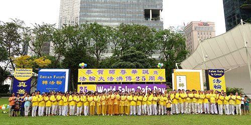 '图1:二零一七年五月二日,新加坡法轮功学员在芳邻公园庆祝即将来临的世界法轮大法日。图为学员们集体合影,虔敬合十,恭祝师尊生日快乐。'