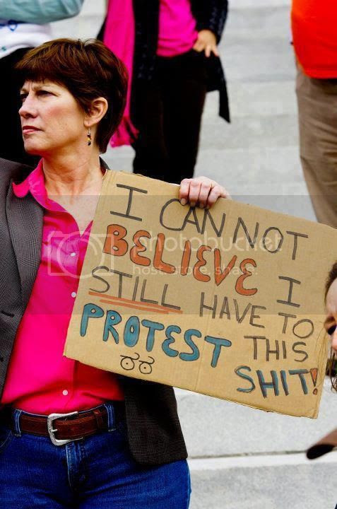 Woman on march holding sign, 'I cannot believe I STILL have to protest this shit!'