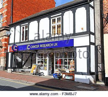 Cancer Research UK front of shop with plastic bags full of