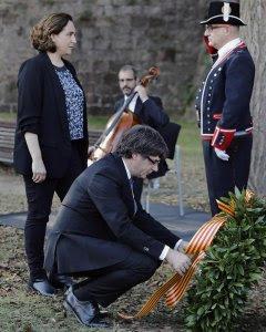 El presidente de la Generalitat, Carles Puigdemont (c), acompañado por la alcaldesa de Barcelona, Ada Colau (i), coloca una corona de flores en el lugar donde el expresident Luís Companys fue fusilado en el fossar de Santa Eulália del Castillo de Montjuic