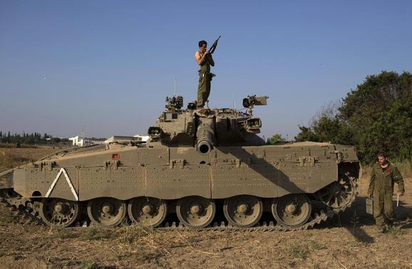 An Israeli soldier checks his weapon atop a tank near the border with Gaza July 27, 2014. REUTERS-Siegfried Modola