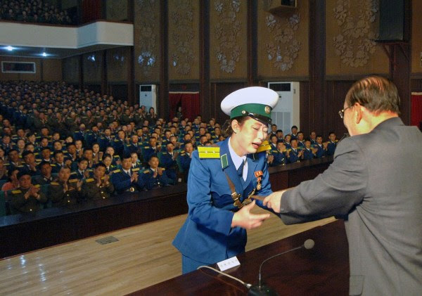"""Pyongyang, North Korea, female traffic officer Ri Kyong Sim crying and wailing as she receives the rare """"Hero of the Republic"""" award and honor for protecting a senior government official."""
