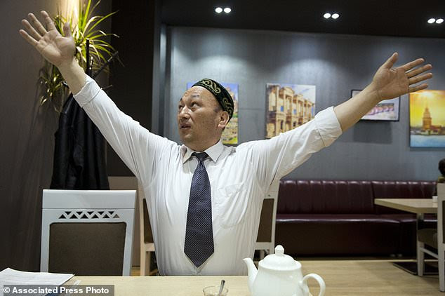 Omir Bekali demonstrates how he was strung up by his arms in Chinese detention before being sent to an internment camp during an interview in Almaty, Kazakhstan.