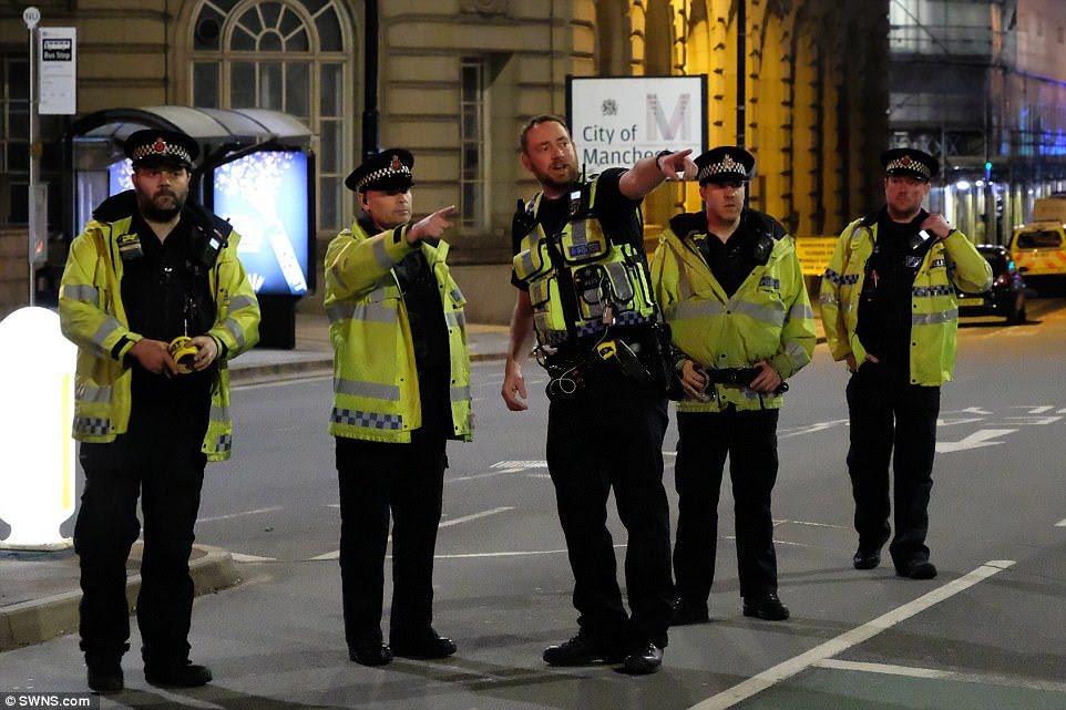 "Police officers stand in a line on a road near Piccadilly Station. Manchester City FC tweeted: ""It's with great sadness we hear of the terrible events at the Arena. Our hearts go out to all affected and to our city's emergency services'"
