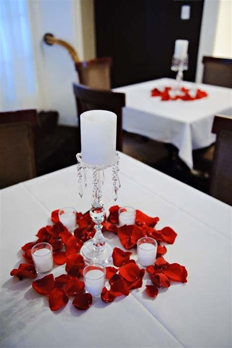 Cocktail table centerpieces: white candles, red rose