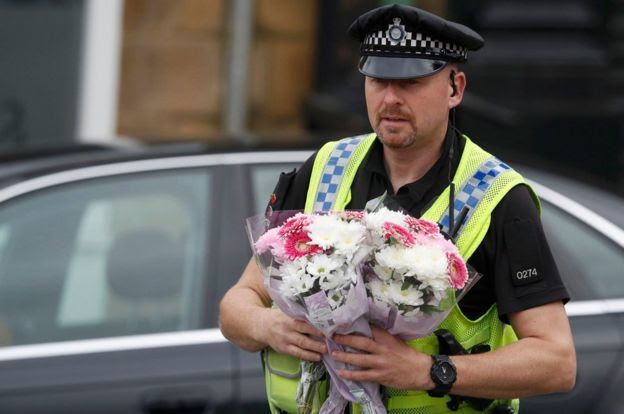 A police officer carries floral tributes