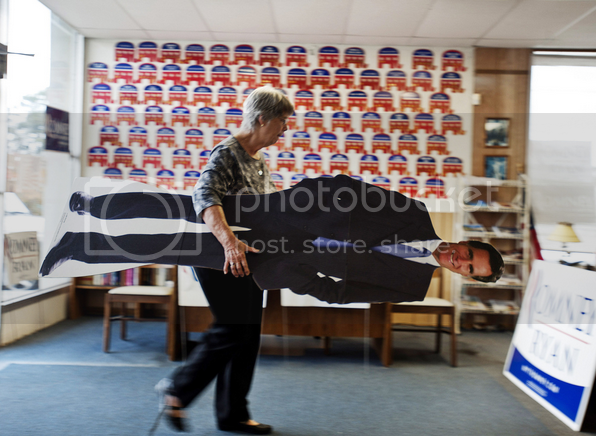Elderly white woman carries away failed presidential candidate Willard Romney.  Or a cardboard cutout of him.  Hard to say.
