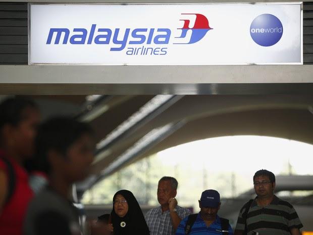 Pessoas passam por anúncio da Malaysia Airlines no Aeroporto Internacional de Kuala Lumpur, em Sepang, Malásia, neste sábado (8). O voo que ia de Kuala Lumpur a Pequim, na China, está desaparecido. Aeronave levava 239 pessoas a bordo. (Foto: Samsul Said/Reuters)