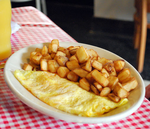 A cheese omelet with home fries.