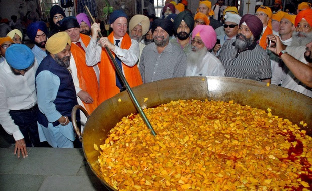Nick Clegg mixes vegetables at a community kitchen during his visit to a Sikh temple in New Delhi, India