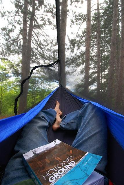 Feet, legs, a book, in a hammock.
