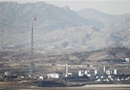 A North Korean flag is flown at half-mast at the propaganda village of Gijungdong near the truce village of Panmunjom in the demilitarized zone separating the two Koreas, in Paju north of Seoul December 22, 2011. REUTERS/Lee Jae-Won