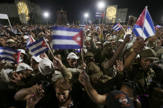 People wave Cuban flags as they attend a... (REUTERS)