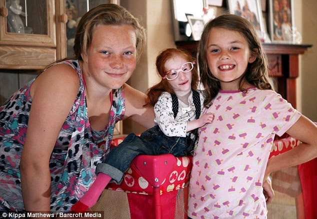 'She might look like a doll but she's made of strong stuff': Charlotte with sisters Sabrina, 12 and Sophie, eight