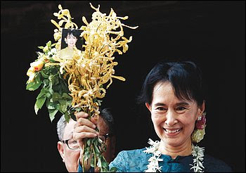 Burmese dissident Aung San Suu Kyi holds flowers before speaking  to supporters. She was released from house arrest Saturday.