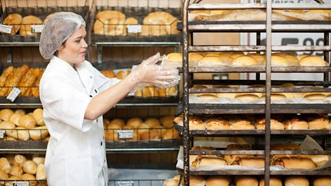 Lady stacking bread