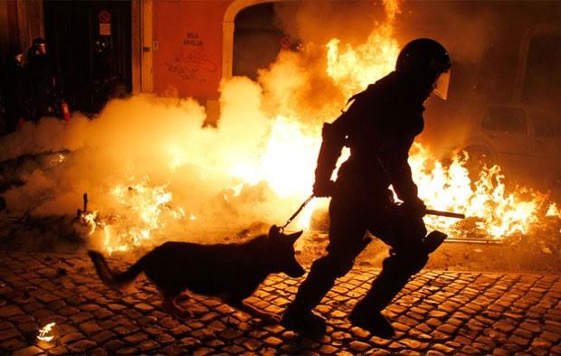 Policial passa por foto ateado por manifestantes durante protesto em Lisboa, Portugal, nesta quarta-feira (14) (Foto: AFP)