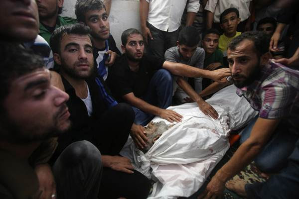 Palestinos cercam o corpo de Hussein Abu al-Naja; médicos disseram que vítima foi morta em um ataque aéreo israelense (Ibraheem Abu Mustafa/Reuters)