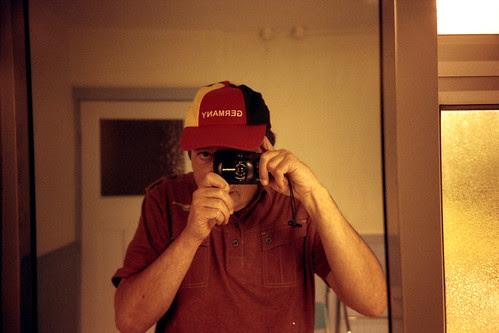reflected self-portrait with Olympus XA4 camera and Germany cap by pho-Tony