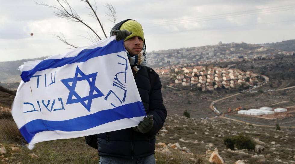 Un colono judío con una bandera isarelí en el asentamiento de Amona en Cisjordania.