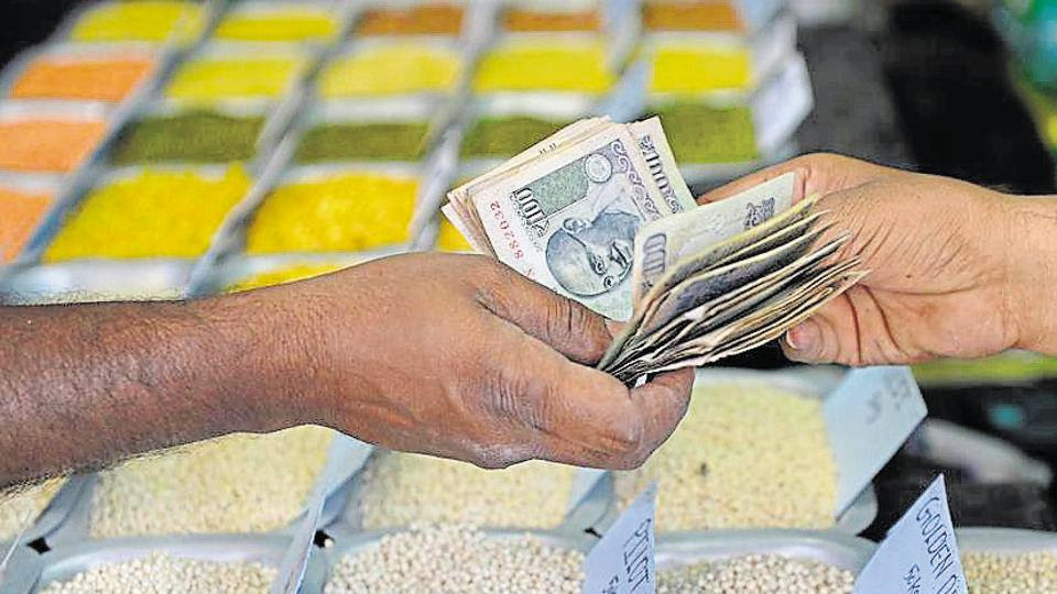 A customer hands over cash to a merchant at a wholesale trading shop in Bengaluru. Indian shares ended higher on August 31, pulling back from losses earlier in the session, as investors awaited GDP data for the April-June quarter.
