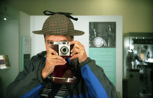 reflected self-portrait with Kodak ColorSnap 35 camera and deer-stalker by pho-Tony