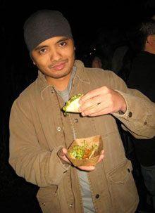 Eating a Kogi BBQ chicken taco.  Yum.
