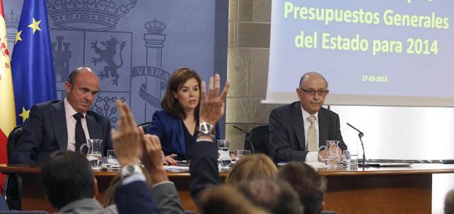 Los ministros de Economía y de Hacienda, Luis de Guindos y Cristóbal Montoro, con la vicepresidenta Soraya Sáenz de Santamaría, en la rueda de prensa tras el Consejo de Ministros en el que se han aprobado los Presupuestos del Estado para 2014.