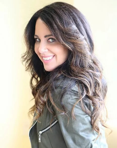 Lainie Ishbia looks at the camera over her left shoulder. She has long black hair and wears a dark leather jacket.
